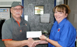 Mr. LeVerne Buck of Hubert, NC is presented with a $250 check from Carrols/Burger King by Becky Switzer, General Manager, Burger King,  Camp Lejeune.