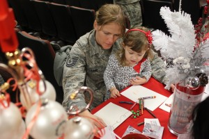 Mom and daughter sign a card for Dad at the holiday card signing kickoff hosted by the Red Cross and 916th air refueling squadron at SeymourJohnson Air Force Base in Goldsboro, NC on Nov. 15 2012