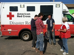 Volunteer Charlotte Rodriguez of Jacksonville, NC (right) helps a group of young men get food and information about Red Cross assistance as they work to clean up storm ravaged homes in Breezy Point, NY.