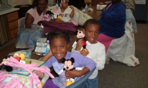 Children from the Fairview Housing Complex fire play with Mickey dolls they received while Red Cross caseworkers met with the families to provide assistance.
