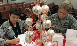 Wayne County Red Cross board member Tara Humphries signs cards with Col. Gilmour of Seymour Johnson Air Force Base