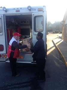 James hands boxes of food to resident Raheem who helps him unload the meals.