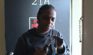 Carla McCray replaces a lock on her fire-damaged apartment.