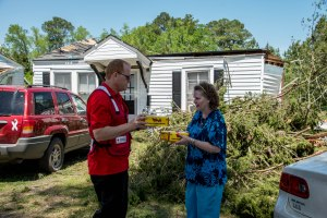 James Jarvis, an American Red Cross volunteer, distributes meals to Mrs. Judy Durbin and her mother following a tornado that destroyed her home.