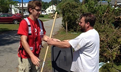 Red Cross volunteer Chase Jarvis hands a rake and clean up supplies to Duncan Blevins whose home was damaged in the tornado.
