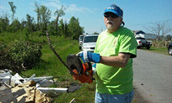 Mason Smith, a member of Kitty Hawk Methodist Church, puts his chainsaw to the test by chopping trees and branches for residents devastated by a tornado last week.
