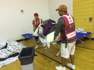 adrian-guerrero-and-son-isaiah-carry-cots-and-in-kind-items-as-they-help-clear-the-westover-shelter-in-fayetteville